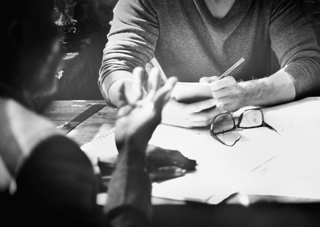 image of people in agency meeting writing notes black and white