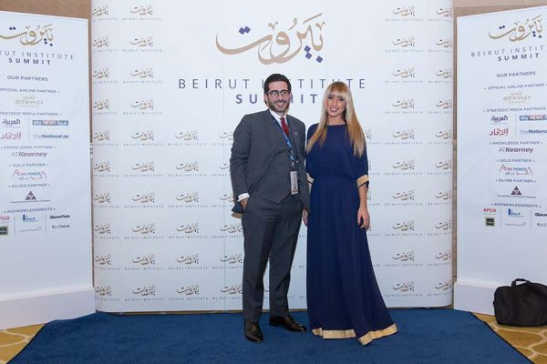 Image of couple standing in front of branded media wall at beirut institute summit event abu dhabi