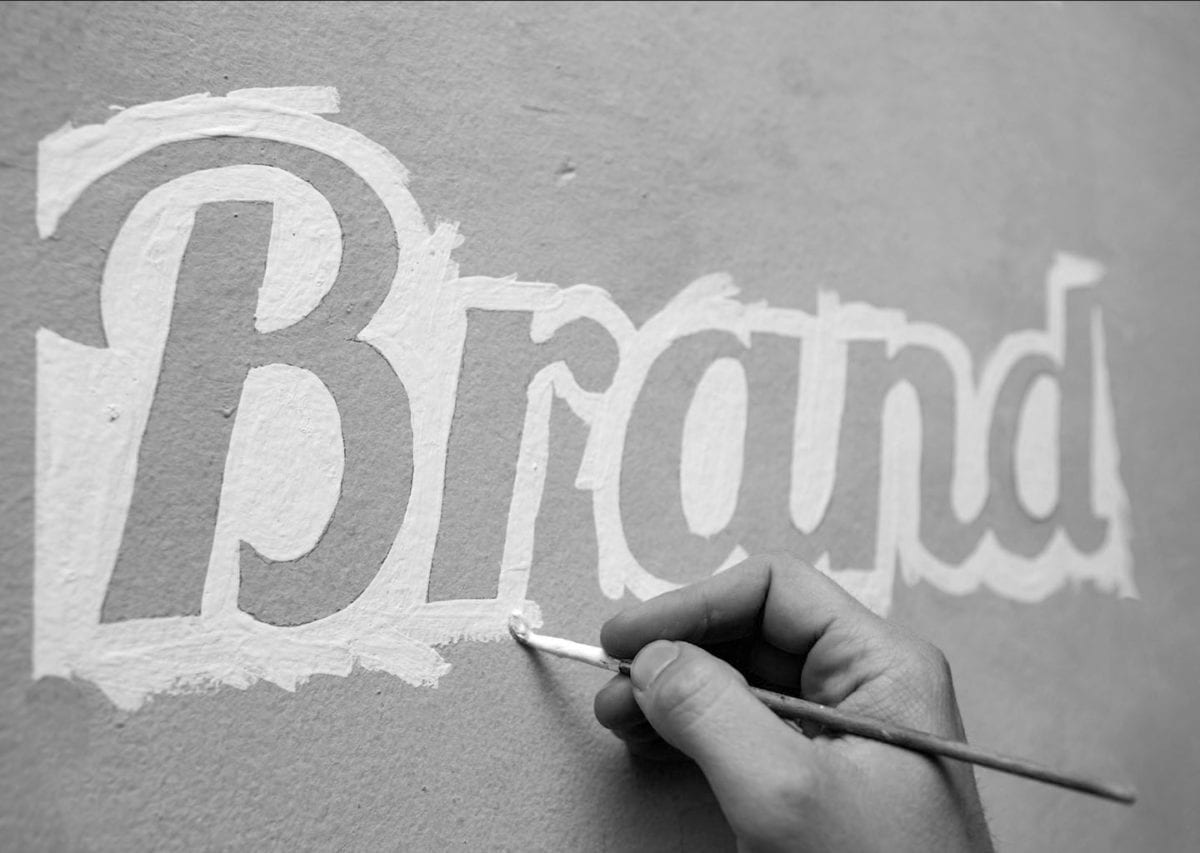 image of someone painting the word brand on a wall