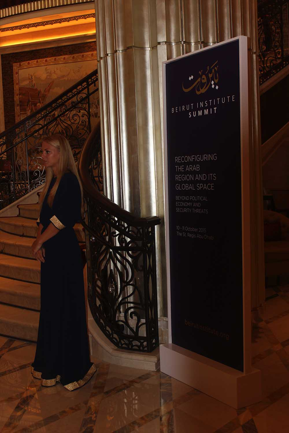 Image of hostess standing next to internal branded way finding at Beirut institute Summit Abu Dhabi
