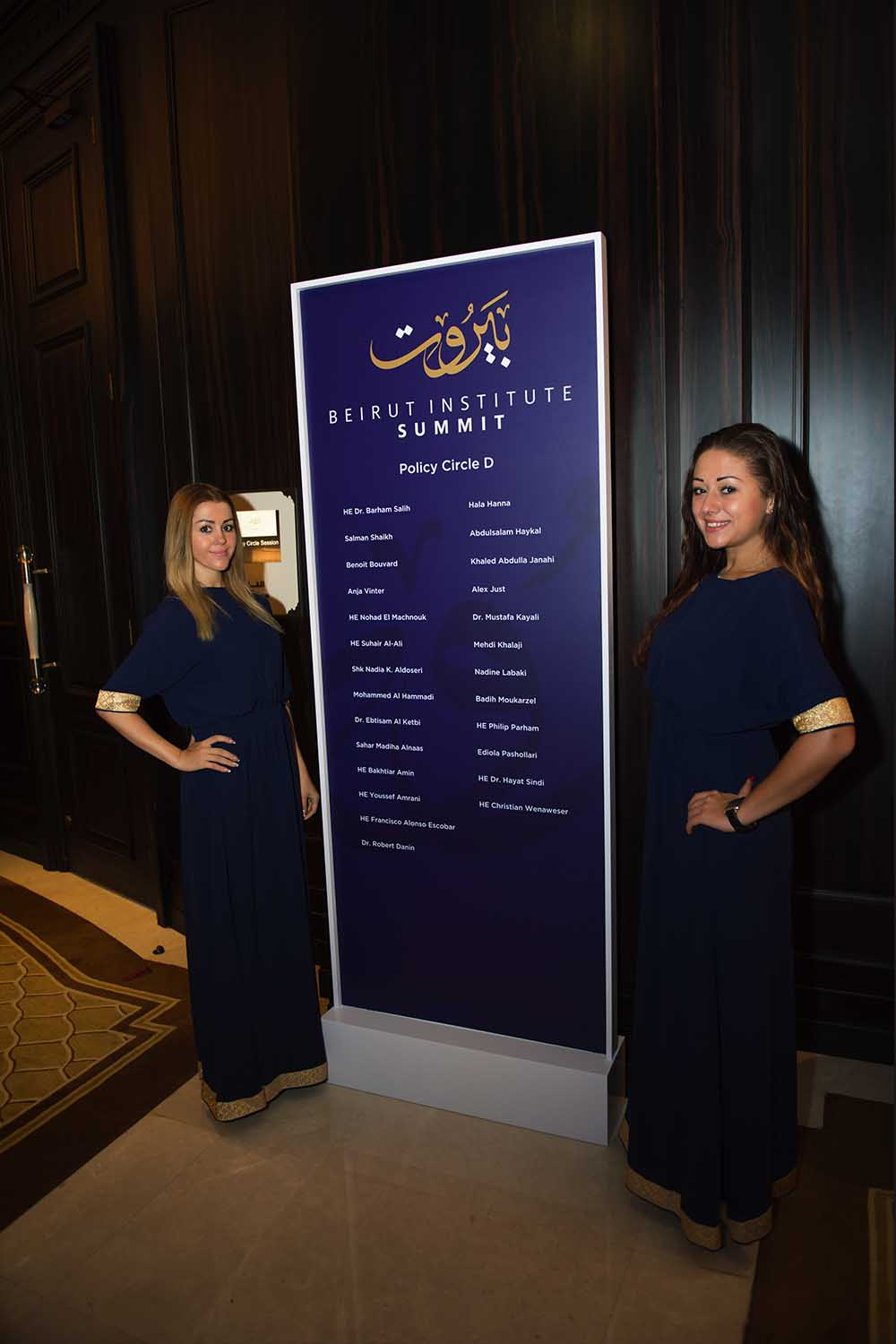 Image of two hostesses standing next to internal branded wayfinding at Beirut institute Summit Abu Dhabi